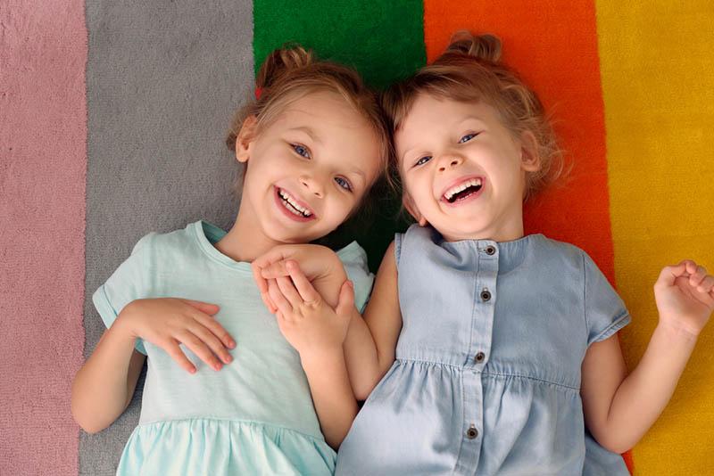 süße kleine Schwestern, die auf einem bunten Teppich liegen und lachen