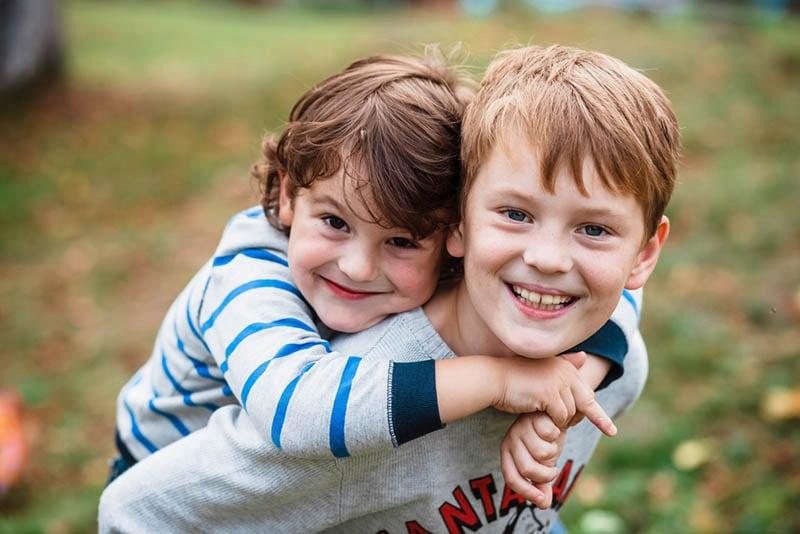 süßer Junge trägt seinen kleinen Bruder auf dem Rücken