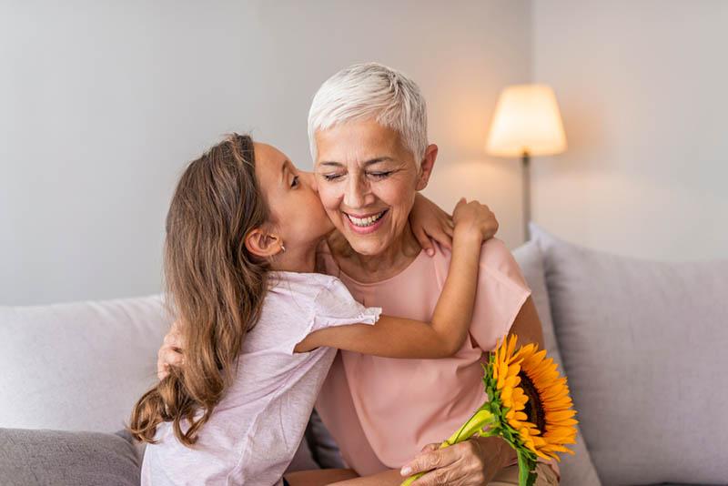 süßes kleines Mädchen küsst ihre Oma zu Hause