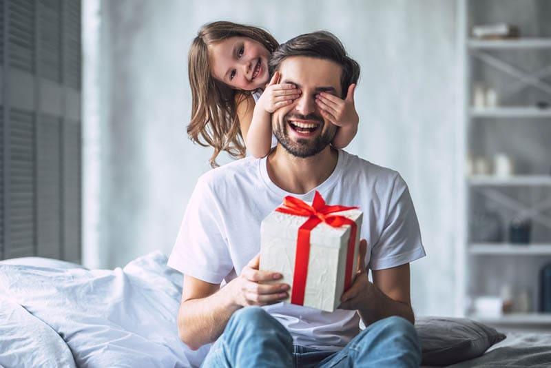 süßes kleines Mädchen überrascht ihren Vater mit Geschenk