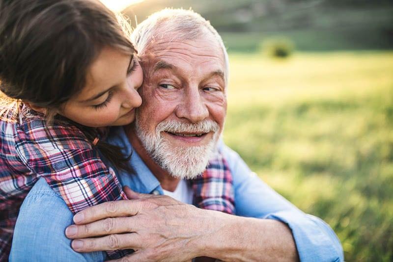 süßes kleines Mädchen umarmt ihren Opa auf dem Feld