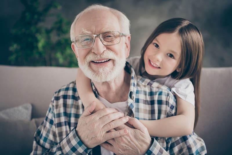 süßes kleines Mädchen umarmt ihren Opa