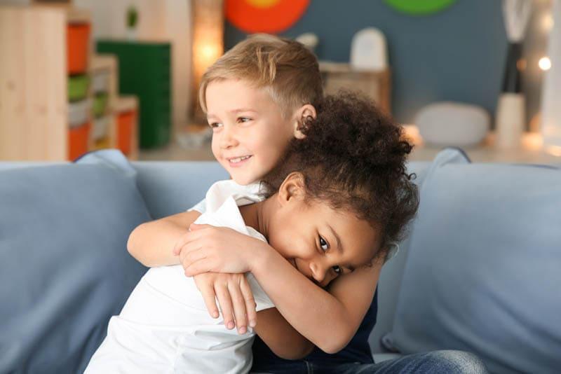 süßes kleines Mädchen umarmt mit ihrem Bruder