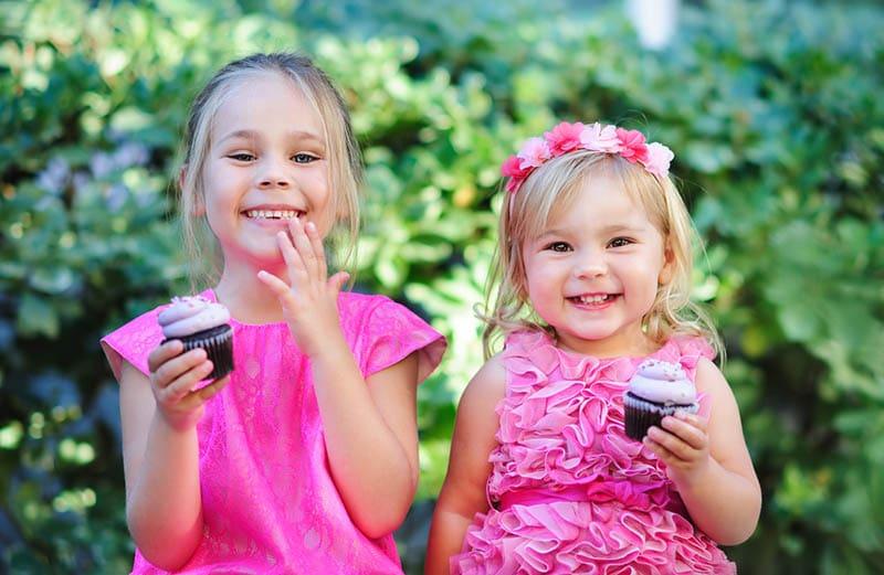 zwei Schwestern essen Geburtstag rosa Cupcake