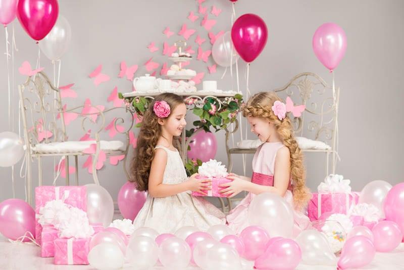 zwei Schwestern sitzen auf dem Boden mit Luftballons und Geschenke für Geburtstag