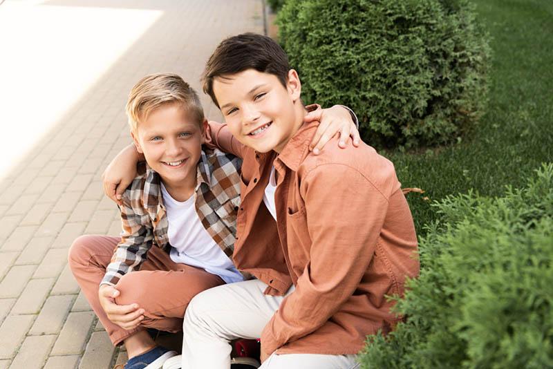 zwei fröhliche Brüder lächelnd beim Sitzen auf dem Bürgersteig