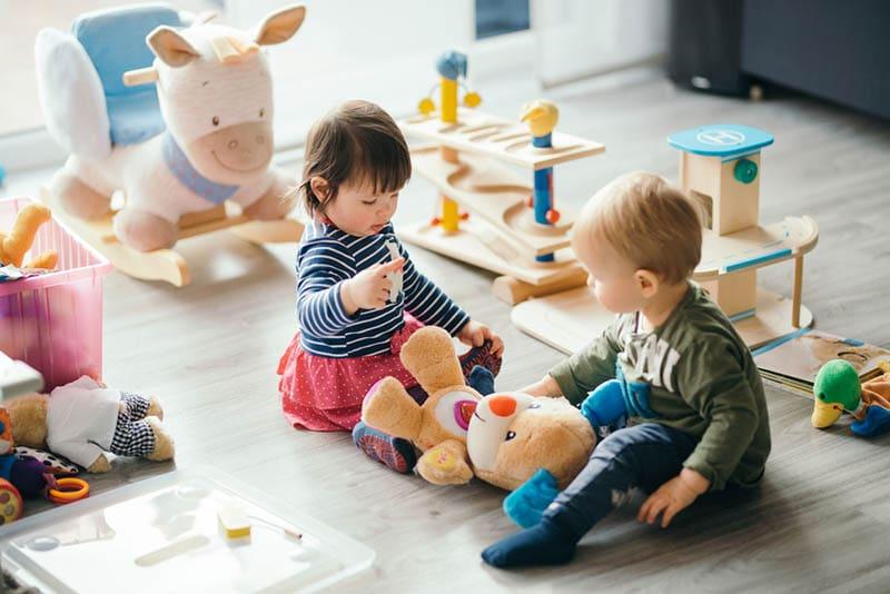zwei niedliche Babys spielen auf dem Boden mit Spielzeug
