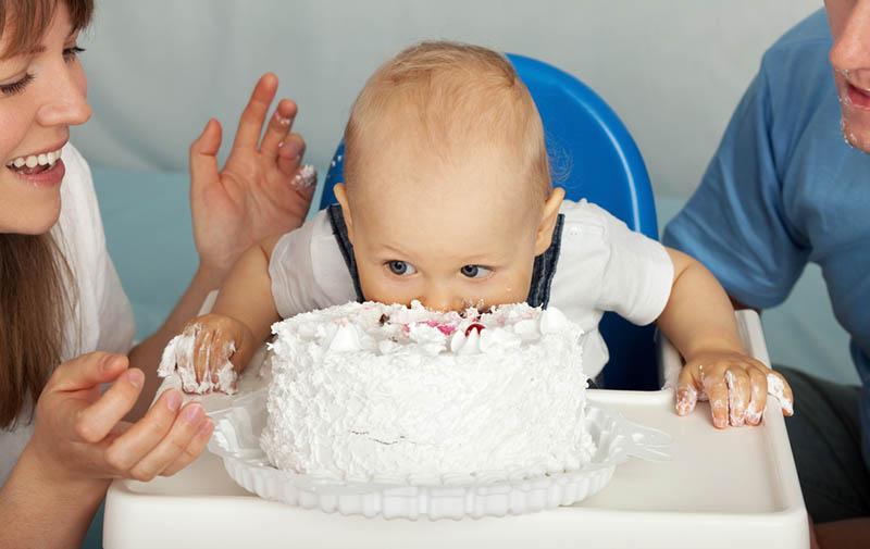 Baby Junge stanzt Gesicht in der Geburtstagstorte