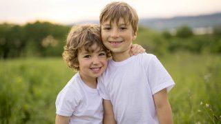 Zwei Bruder posiert zusammen in einer grünen Wiese