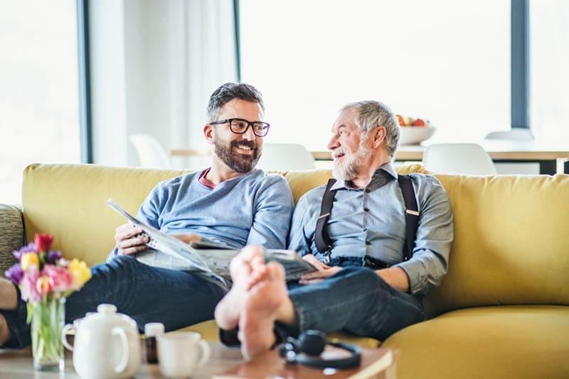 Ein erwachsener Hipster-Sohn und ein älterer Vater sitzen auf dem Sofa zu Hause