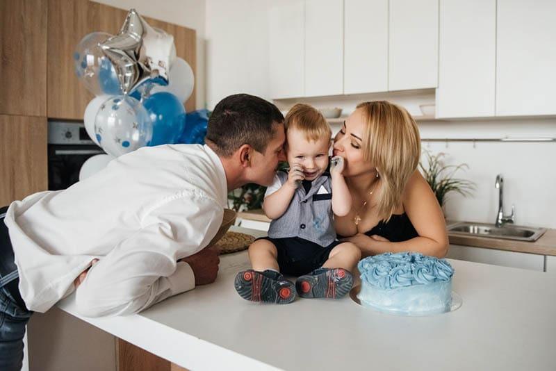 Eltern küssen Baby Junge zum Geburtstag zu Hause