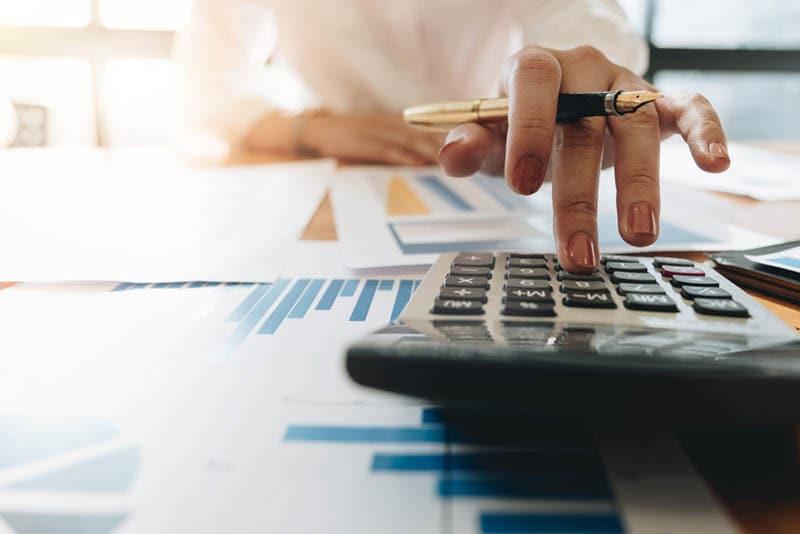 Frau mit Taschenrechner und Laptop für Finanzen