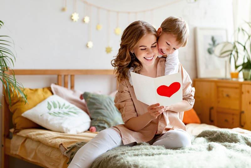Fröhliche Mutter umarmt Sohn und Lesen handgemachte Grußkarte
