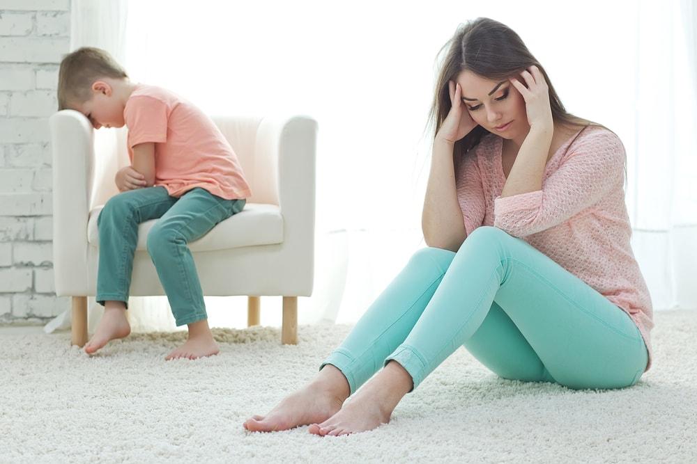 Frustrierte junge Mutter sitzt auf dem Boden, während ihr Kind im Hintergrund ist