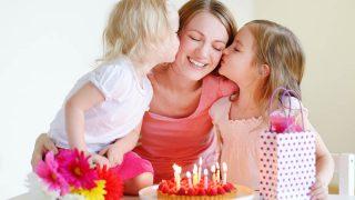 zwei kleine Mädchen geben ihrer Mutter zum Geburtstag einen Kuss auf die Wange
