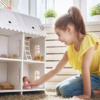 Süßes kleines Mädchen spielt mit einem Puppenhaus