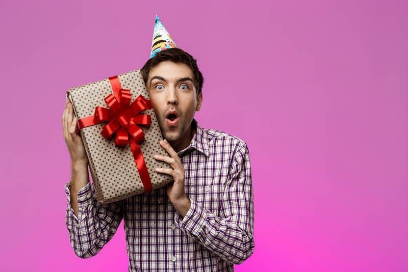 Glücklicher junger Mann hält Geburtstagsgeschenk in Box