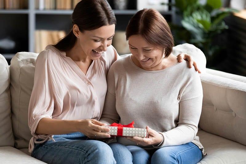 Junge Frau gibt Geschenk an ihre Mutter