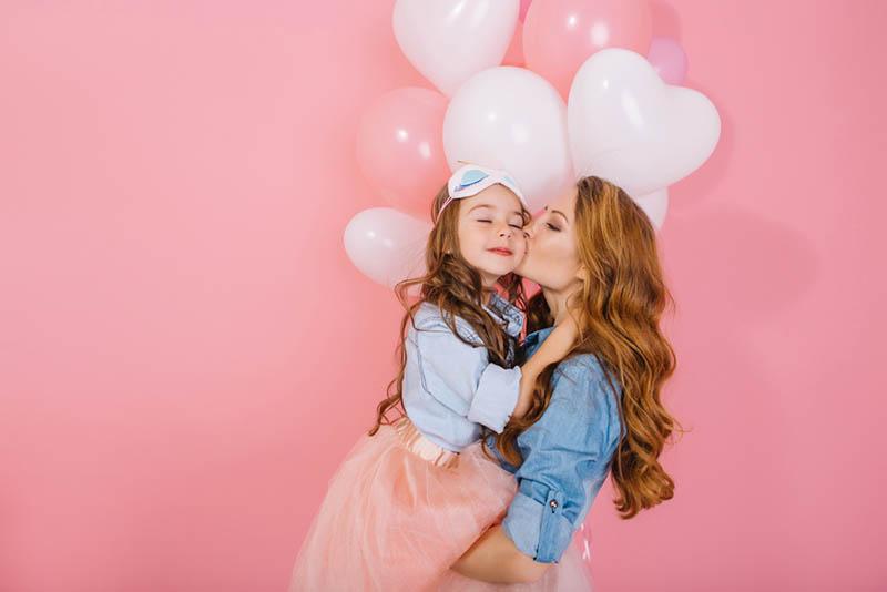 Junge Frau küsst ihre kleine Tochter an ihrem Geburtstag