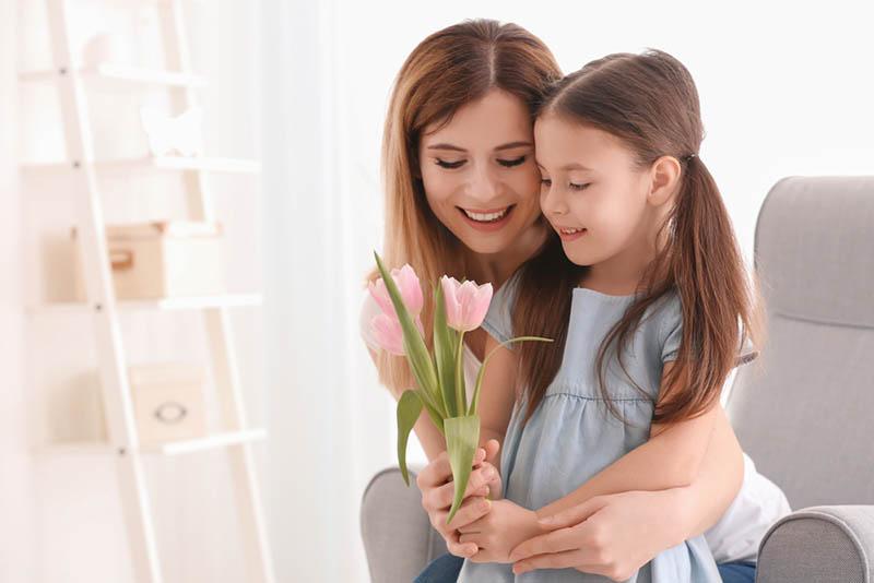 Junge Mutter gibt Blumen zu ihrer süßen Tochter