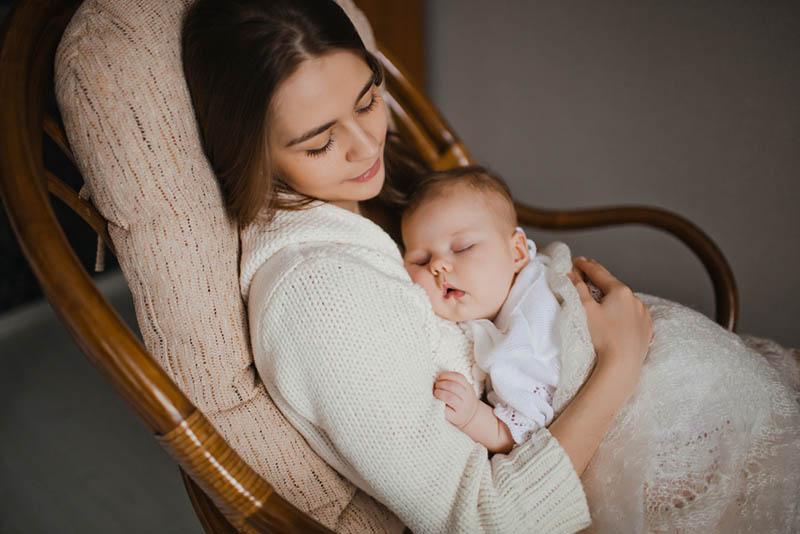 Junge Mutter hält ihr schlafendes Baby mit einer Decke bedeckt, während sie in einem Schaukelstuhl sitzt