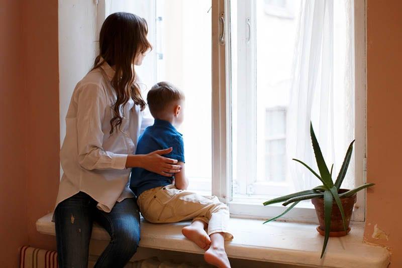 Junge traurige Mutter mit Sohn Kind sitzt auf Fenster
