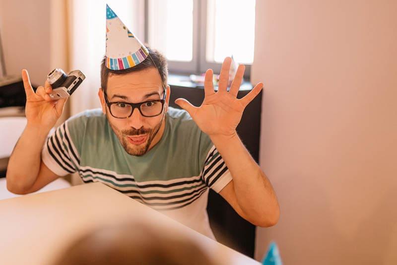 Junger Vater mit Partyhut macht lustige Gesichter