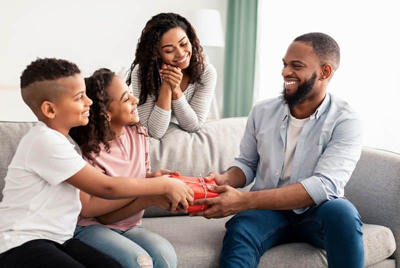 Kinder und ihre Mutter gratulieren Papa und geben ihm ein Geburtstagsgeschenk
