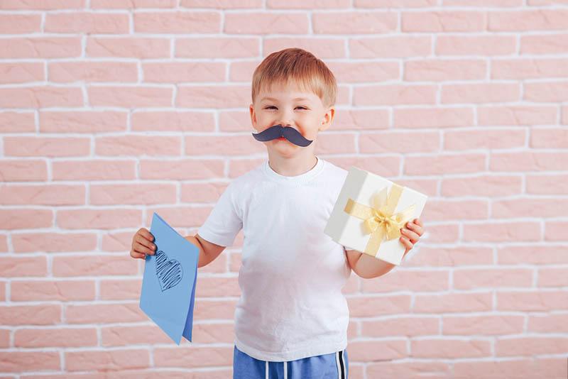 Kleiner Junge mit Schnurrbart hält ein Geschenk in seinen Händen