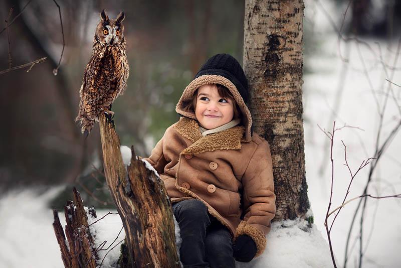 Kleiner Junge schaut auf Eule draußen auf dem Schnee