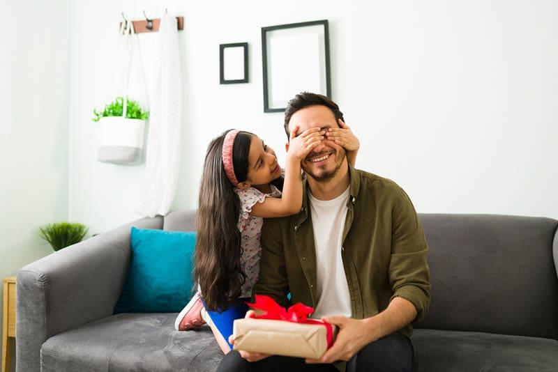 Kleines Mädchen, das ihrem Vater die Augen zuhält, um ihm ein Überraschungsgeschenk zu machen
