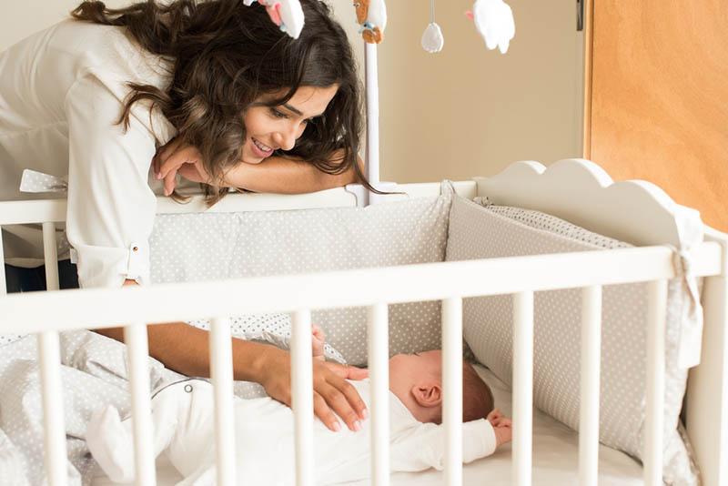 Lächelnde Mutter kümmert sich um ihr Baby in der Krippe zu Hause