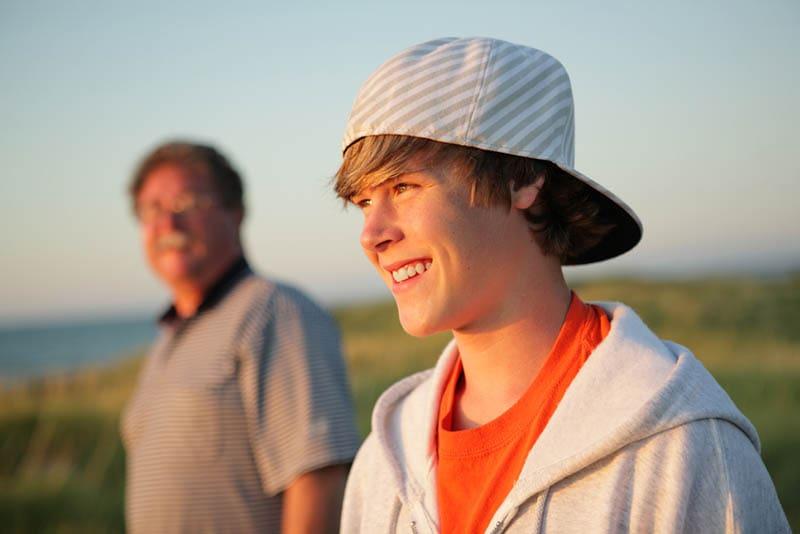 Lächelnder Teenager mit Vater auf einer Wanderung
