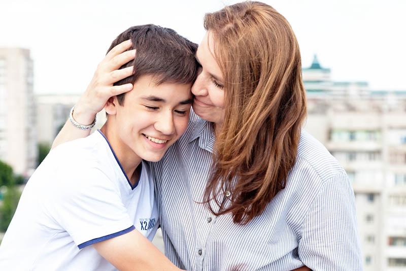 Mutter, die ihren lächelnden Teenager-Jungen umarmt