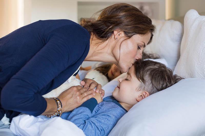 Mutter gibt dem schlafenden Sohn einen Gute-Nacht-Kuss