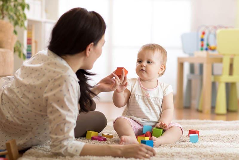 Mutter spielt mit ihrem Baby Mädchen auf dem Boden zu Hause mit Holzwürfeln