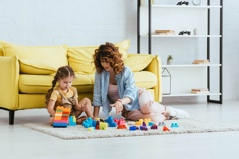Mutter und Tochter spielen mit Bauklötzen auf dem Boden zu Hause