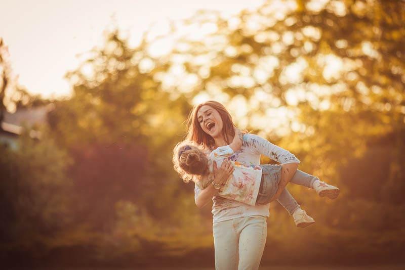 Mutter und kleine Tochter spielen zusammen in einem Park
