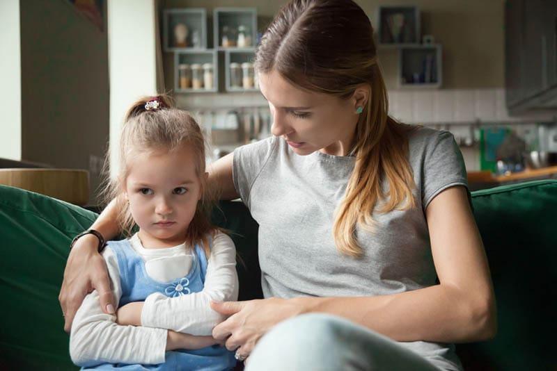 Mutter versucht, mit wütendem kleinen Mädchen zu reden