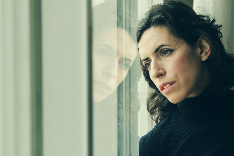 Nachdenkliche Frau schaut aus dem Fenster