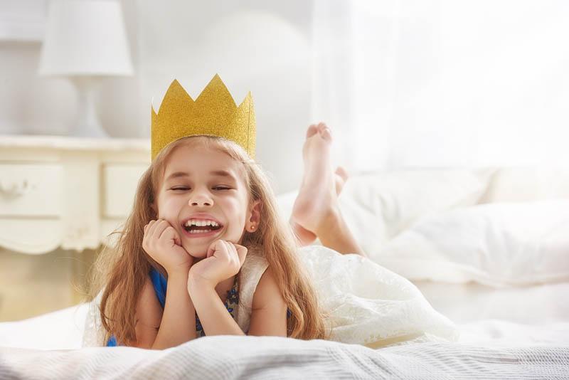 Nettes kleines Mädchen in einem Prinzessinnenkostüm mit Krone auf dem Bett liegend