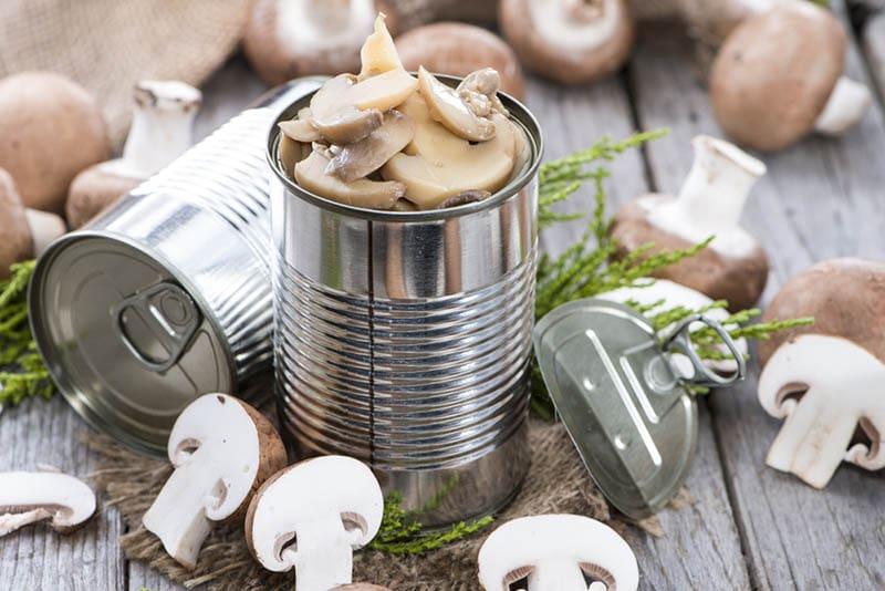Pilzkonserven mit Champignons auf dem Holztisch