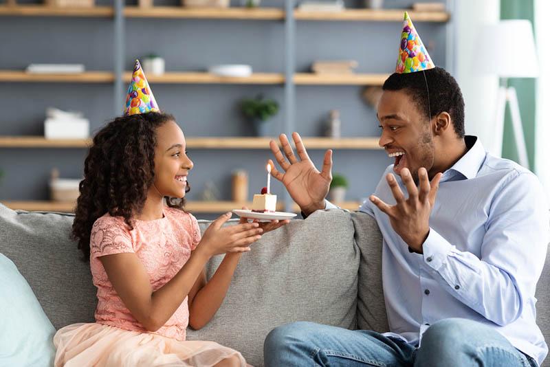 Schönes Mädchen hält Geburtstagskuchen mit beleuchteten Kerze für ihren aufgeregten Vater