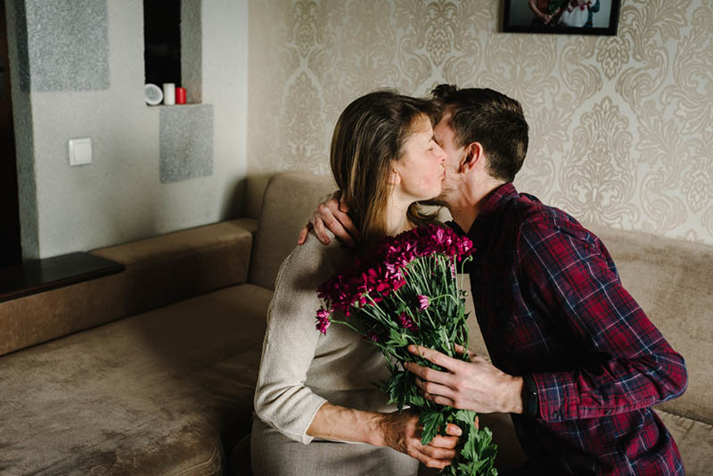 Sohn küsst seine Mutter und schenkt ihr Blumen