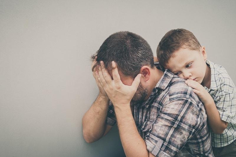 Sohn umarmt seinen frustrierten Vater