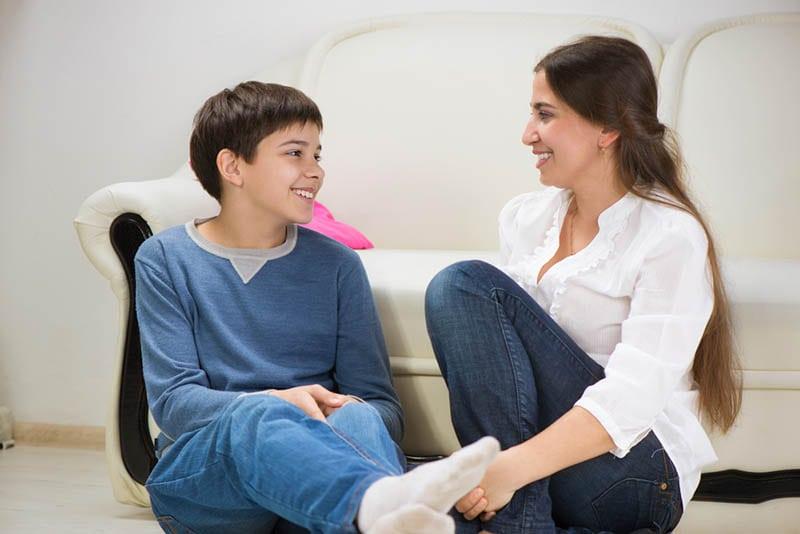 Teenager-Junge mit Mutter im Gespräch auf dem Boden