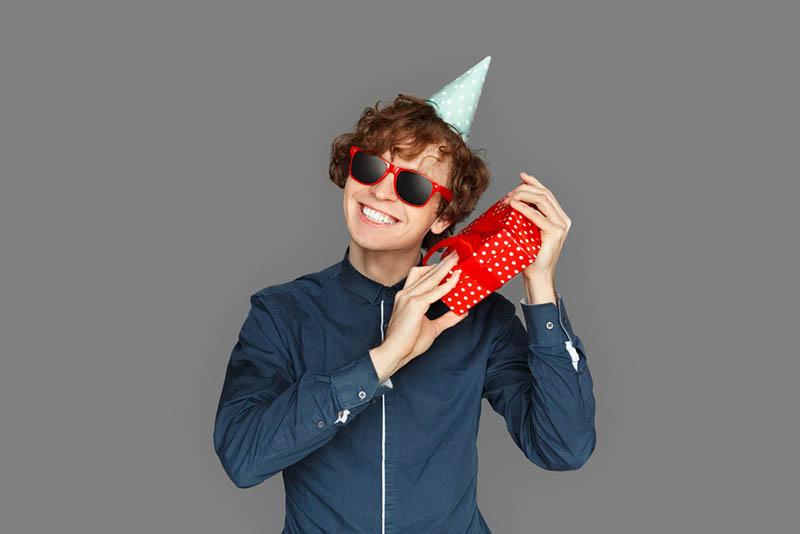 Teenager Junge trägt Geburtstagskappe und Sonnenbrille und hält ein Geschenk
