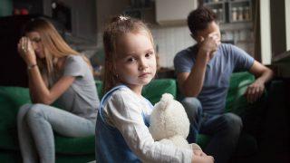 kleines Mädchen hält ein Spielzeug, während ihre Eltern durch eine Trennung gehen