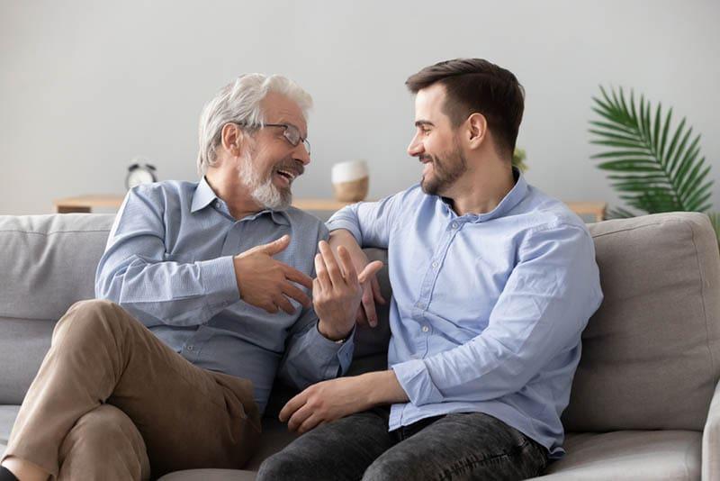 Vater im Gespräch mit seinem erwachsenen Sohn auf der Couch