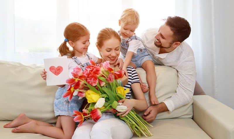 Vater und Kinder gratulieren Mutter zum Geburtstag